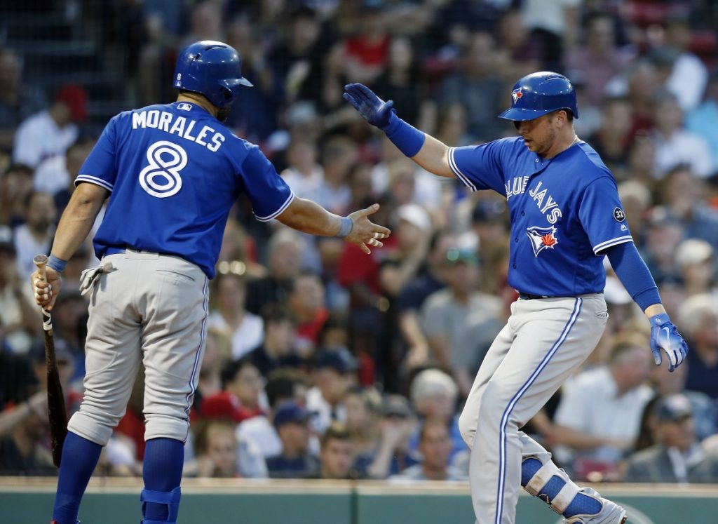 Justin Smoak, right, celebrates the first of his two home runs with Kendrys Morales during Toronto's 13-7 win over the Red Sox on Friday night.