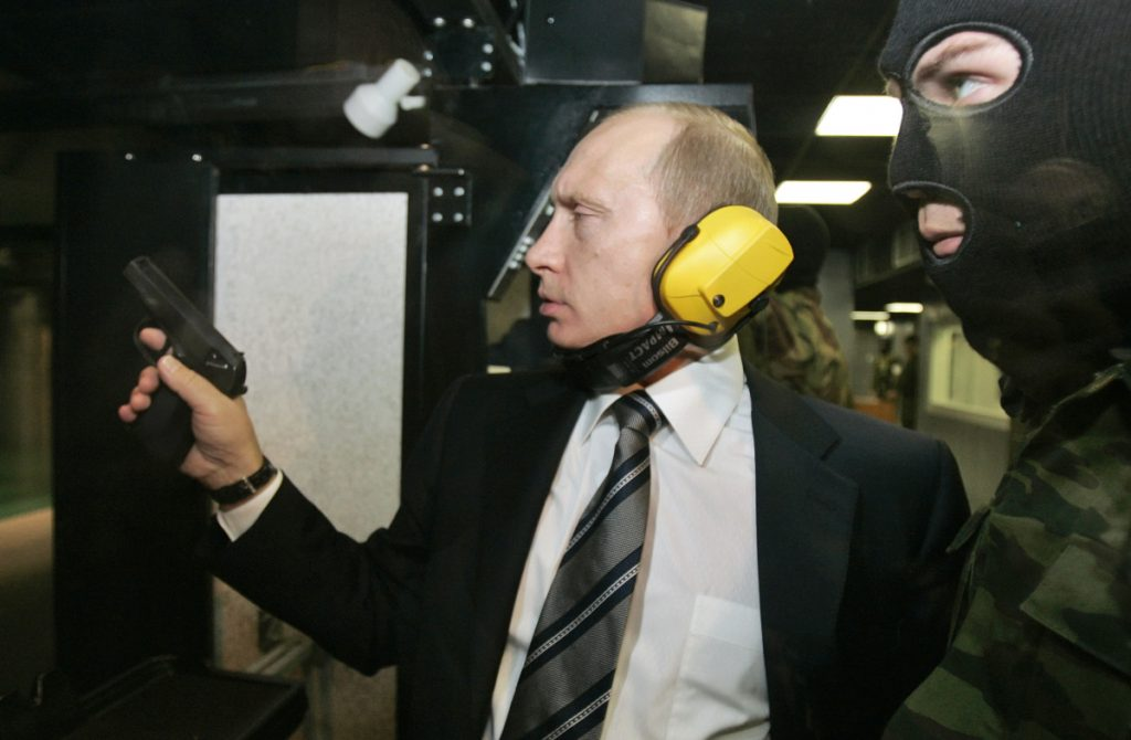 Russian President Vladimir Putin wears headphones as he tests a pistol in a shooting range at the Defense Ministry's Main Intelligence Directorate in Moscow.