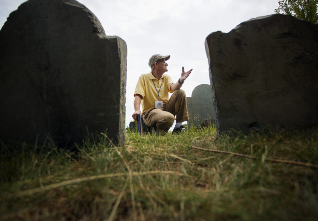 PORTLAND, ME - JULY 14: Volunteer Dave Smith kneels between gravestones while giving a tour of Eastern Cemetery in Portland on Saturday, July 14, 2018. The hour-long tours, at 11 a.m. on Saturdays, Wednesdays, Sundays and 5:30 p.m. on Thursdays, are part of summer offerings during the cemetery's 350th annivesary. (Photo by Derek Davis/Staff Photographer)