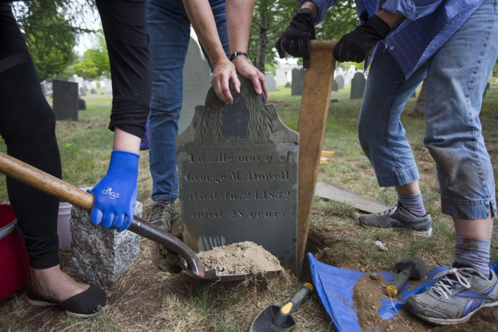 Members of Spirits Alive, a nonprofit group formed 11 years ago to restore and preserve the cemetery, reset a gravestone Saturday after restoring it and reuniting it with the footstone, which was recently recovered near the Dead House.