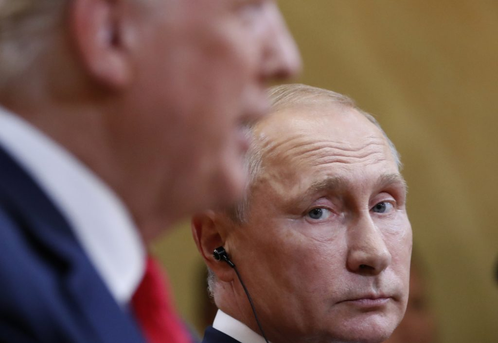 Russian President Vladimir Putin listens to President Trump during a news conference Monday after their meeting in Helsinki, Finland. Trump tried to walk back some of his comments Tuesday.