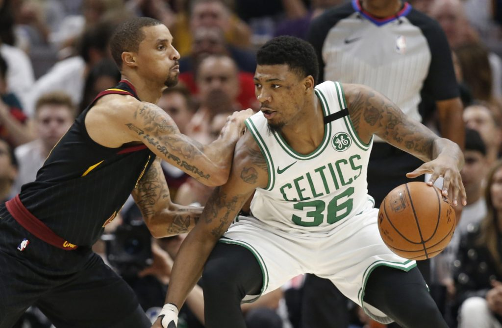 Boston's Marcus Smart, right, drives past Cleveland's George Hill during Game 6 of the NBA's Eastern Conference finals in May. (AP Photo/Ron Schwane)