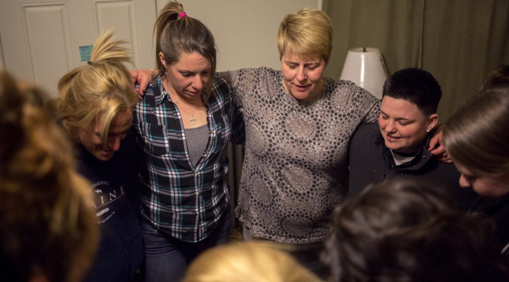 Nichole Curtis, center, who runs a Portland sober house, takes part in the prayer at the end of a 2017 meeting. Maine doesn't regulate sober-living homes or even keep track of where they're located.