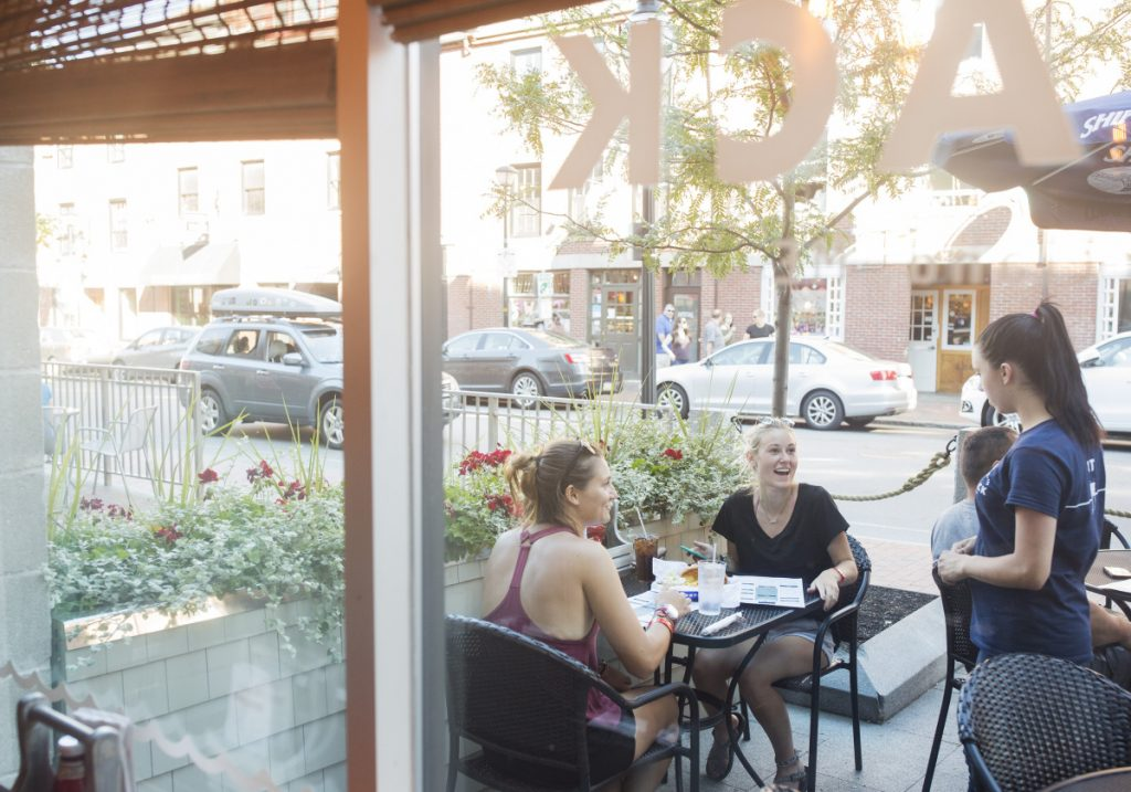 Ellie Napoli, left, and Darian Blevins talk with their server on the inviting patio at Maine Lobster Shack. The restaurant opened in April on Fore Street in Portland's Old Port.