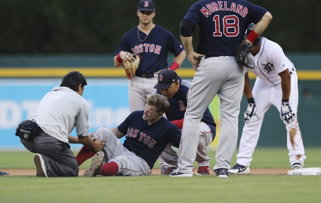 Boston second baseman Brock Holt is examined after colliding with Detroit's Jeimer Candelario in the fourth inning Friday night in Detroit. Holt had to leave the game with a knee contusion.