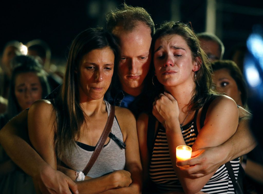 Mallory Cunningham, left, Santino Tomasetti, center, and Aubrey Reece attend a candlelight vigil in the parking lot of Ride the Ducks on Friday, in Branson, Mo.
