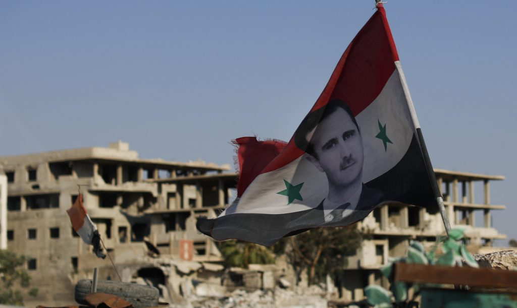 A Syrian flag with the picture of President Bashar Assad hangs at an Army checkpoint in Douma, Syria, on Sunday. Rescue workers known as the White Helmets, considered terrorists by Syria and Russia, were trapped near the Israeli border.