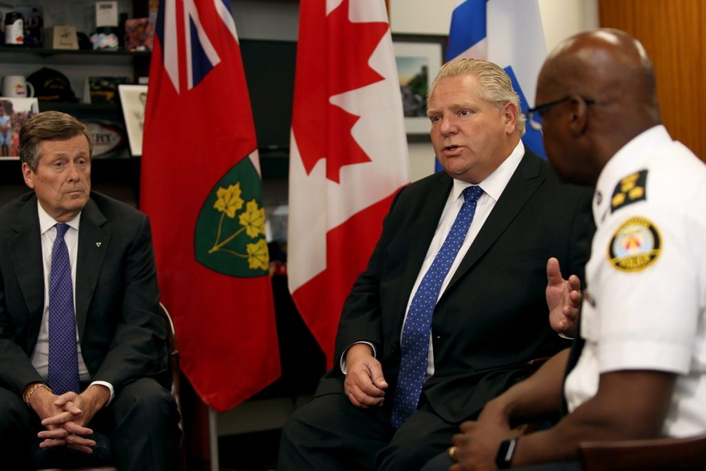 Toronto mayor John Tory, left, and Police Chief Mark Saunders, right, look on as Ontario Premier Doug Ford speaks during an intergovernmental meeting at Toronto City Hall on Monday in the wake of a mass shooting which happened in Toronto on Sunday night.