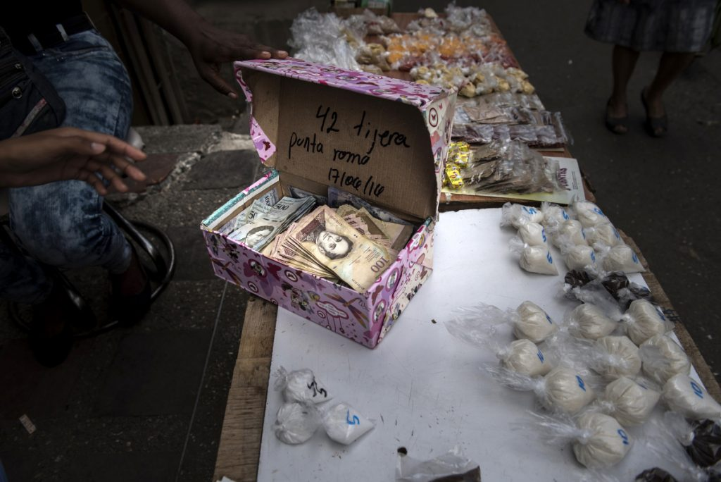 A street vendor opens a box of Bolivar banknotes at a stand in the Petare slum of Caracas, Venezuela. The country's economy has been broken by corruption, failed socialist policies and a collapsing oil industry.