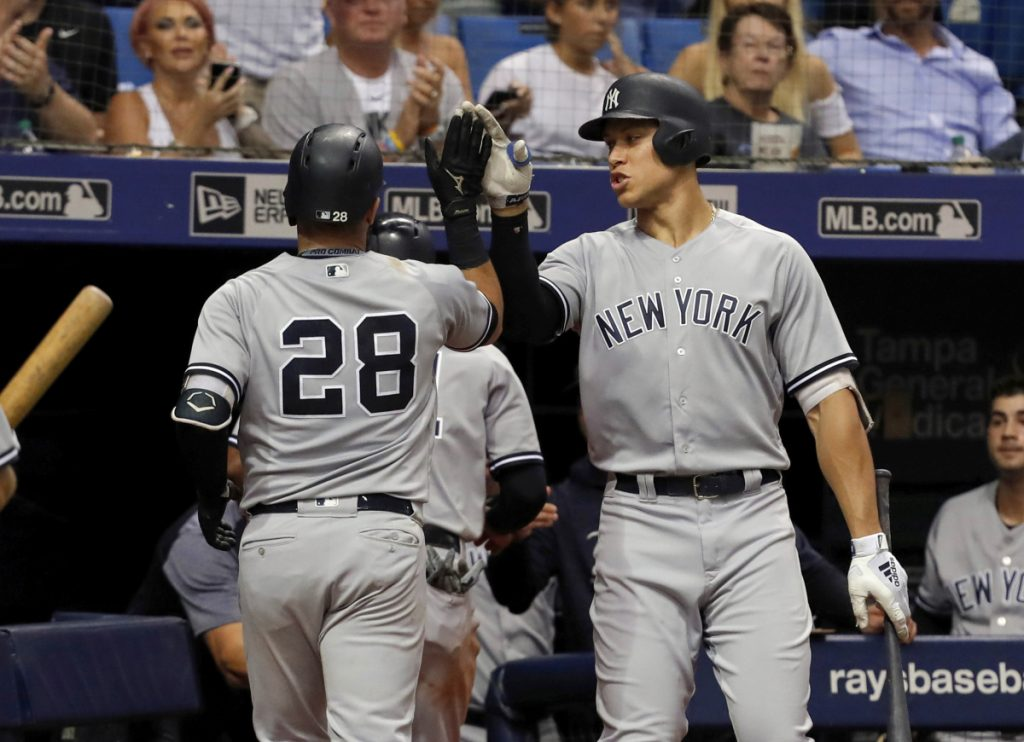 Austin Romine of the New York Yankees, left, is welcomed by Aaron Judge after hitting a sacrifice fly Tuesday night in the seventh inning of a 4-0 win over the Tampa Bay Rays