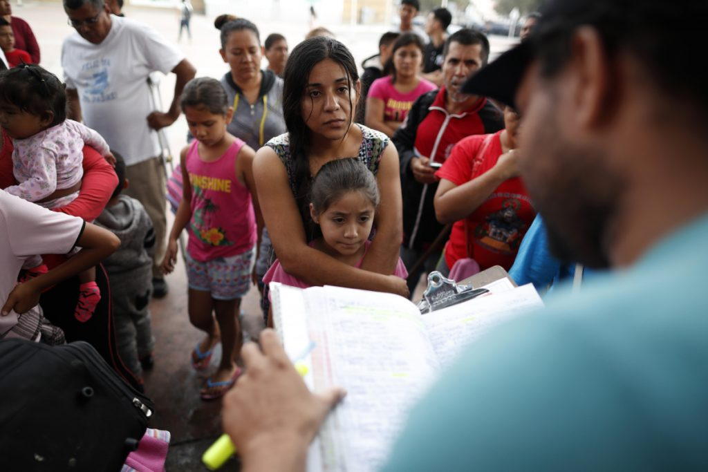A woman from the Mexican state of Michoacan who did not give her name stands with her daughter as names are read off a list of people who will cross into the United States to begin the process of applying for asylum Thursday near the San Ysidro port of entry in Tijuana, Mexico. As the Trump administration faced a court-imposed deadline Thursday to reunite thousands of children and parents who were forcibly separated at the U.S.-Mexico border, asylum seekers continue to arrive to cities like Tijuana, hoping to plead their cases with U.S. authorities.