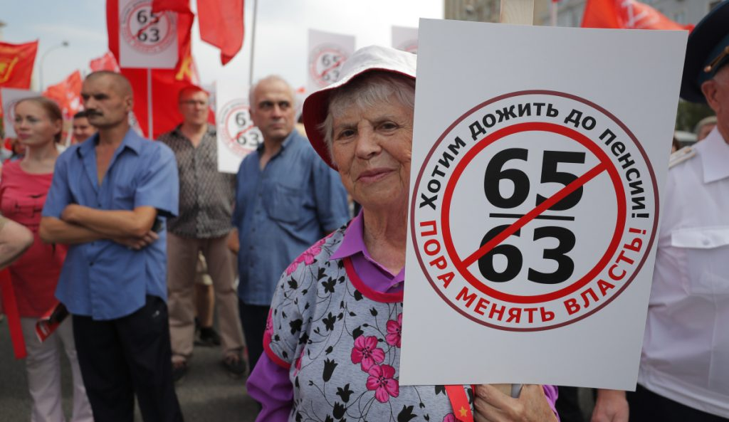 "A Russian woman makes her feelings known with a sign that reads, ""Want to Retire, it's time to change the authority!"" during a rally protesting retirement age hikes in Moscow on Saturday."
