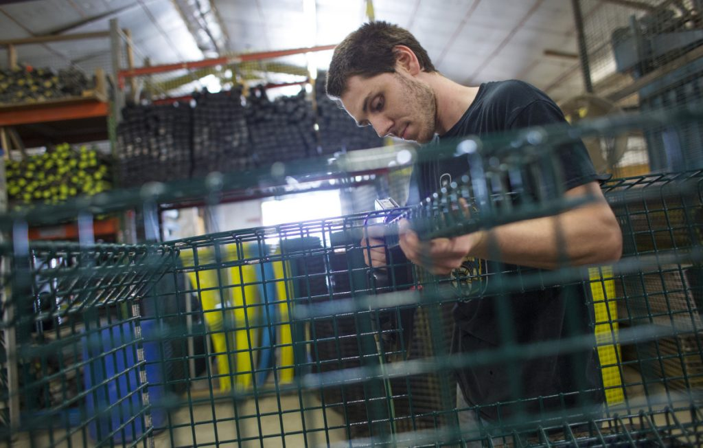 Dustin Chamberlain assembles the cage of an offshore lobster trap at Friendship Trap Co.
