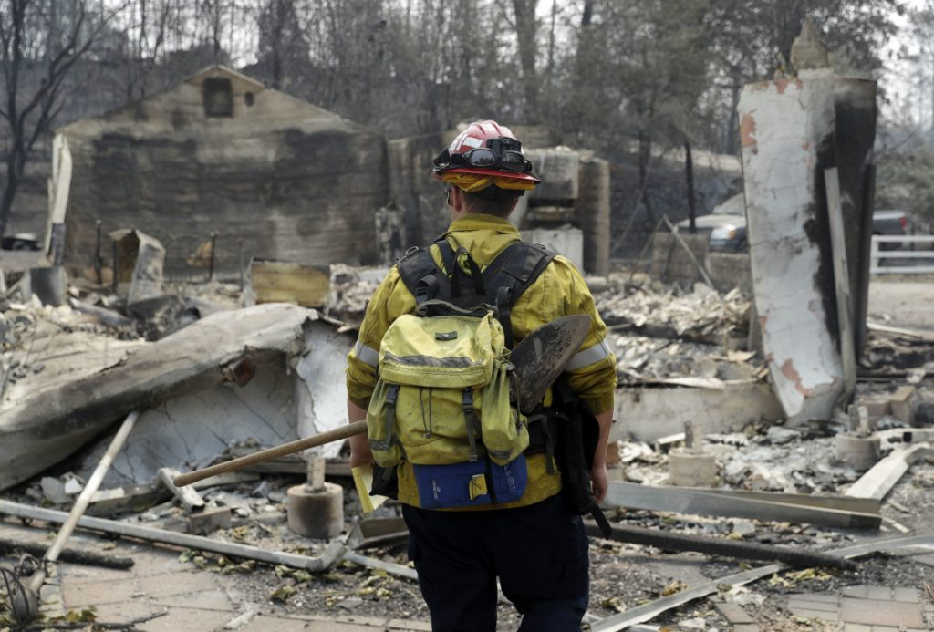 Capt. Scott Fisher, with the San Bernardino County Fire Department, surveys a wildfire-damaged neighborhood Sunday in Keswick, Calif.