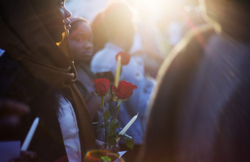 Samar Ahmed of Portland holds roses during Tuesday night's vigil for Patrick Lobor.
