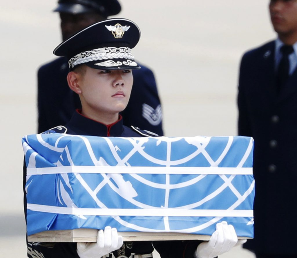 A soldier carries a box holding what North Korea says is the remains of a U.S. soldier killed in the Korean War.