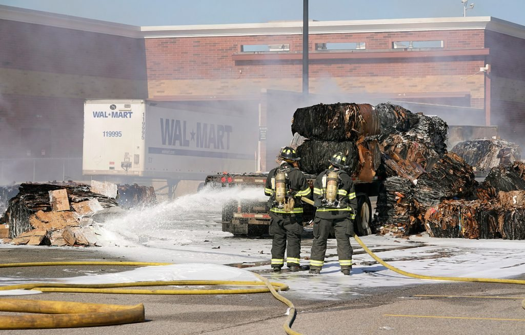 Scarborough firefighters spray foam on a pile of cardboard behind the Walmart in Scarborough on Thursday. Smoke from the fire entered the store, causing it to be evacuated.