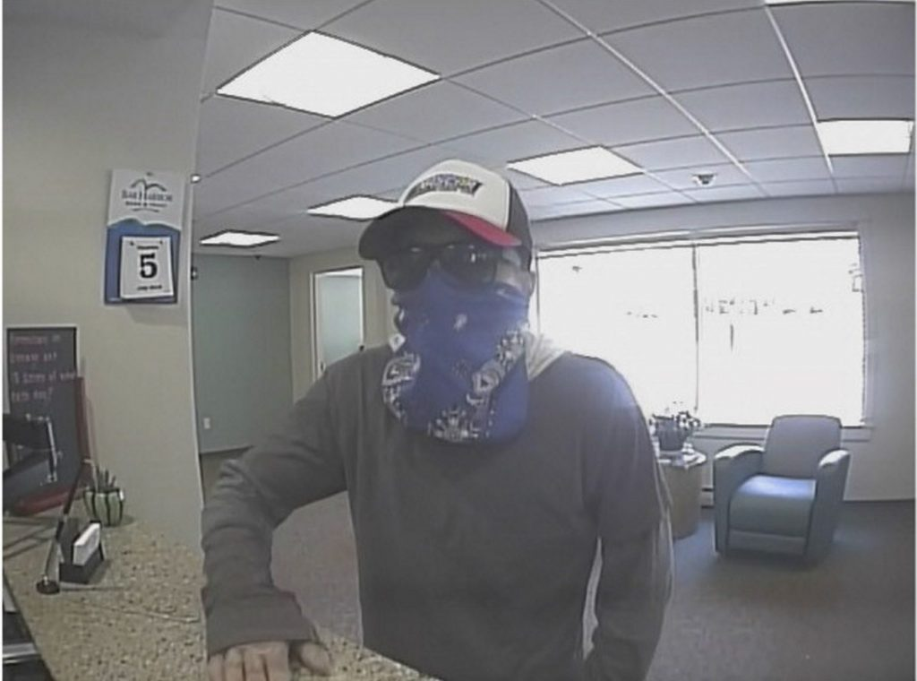 The suspect in the hold up of Bar Harbor Bank and Trust on Route 3 in South China is described as a white male about 5 feet 3 inches with dark hair, dark eyebrows and a slim build. He wore a dark gray longsleeve shirt, dark blue jeans, a blue bandanna, black sunglasses, dark sneakers and a black-and-white baseball hat with a red bill.