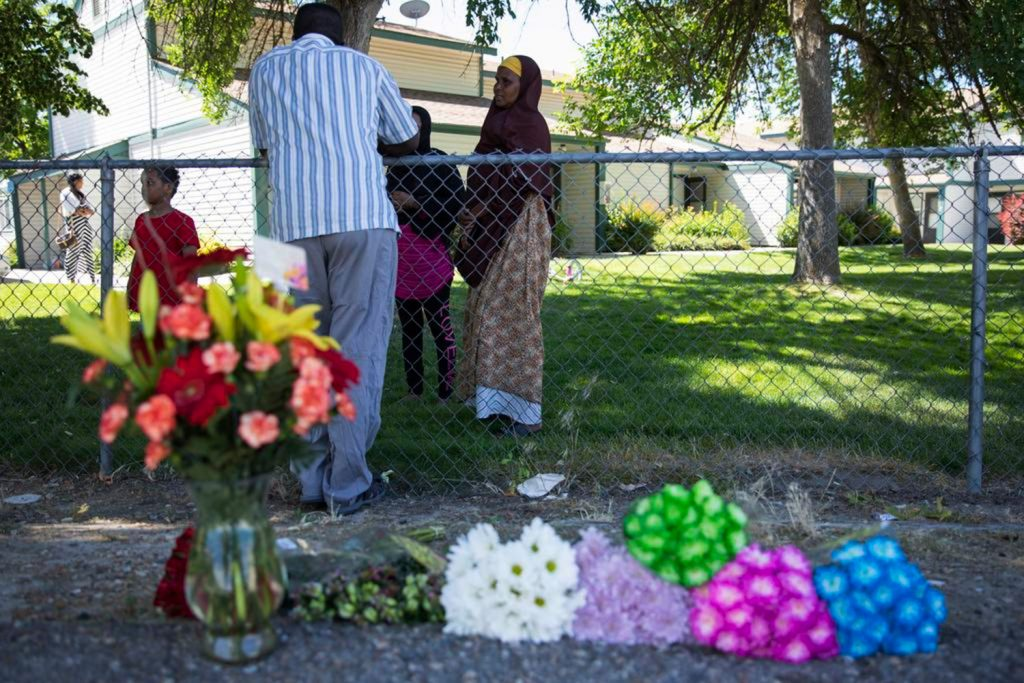 Ibod Hasn, center, talks to a friend who came to visit after Saturday's stabbing attack in Boise, Idaho, on Sunday. A man who had been asked to leave an Idaho apartment complex because of bad behavior returned the next day and stabbed people, including several children, at a toddler's birthday party, police said.