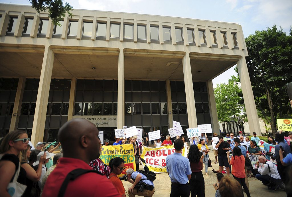 People hold a rally outside the Federal Courthouse in Bridgeport, Conn. on Wednesday, July 11, 2018. Lawyers for two immigrant children detained in Connecticut after being separated from their parents at the U.S.-Mexico border asked a federal judge on Wednesday to order that the girl and boy be reunited with their families.