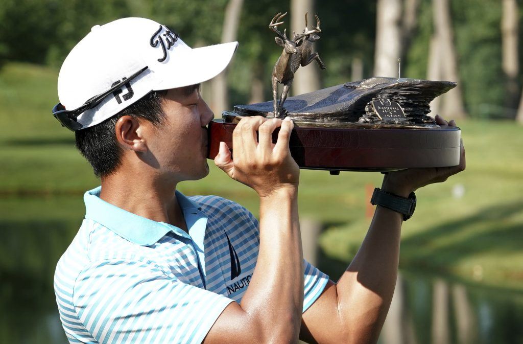 Michael Kim kisses the trophy after winning the John Deere Classic on Sunday at TPC Deere Run in Silvis, Ill.