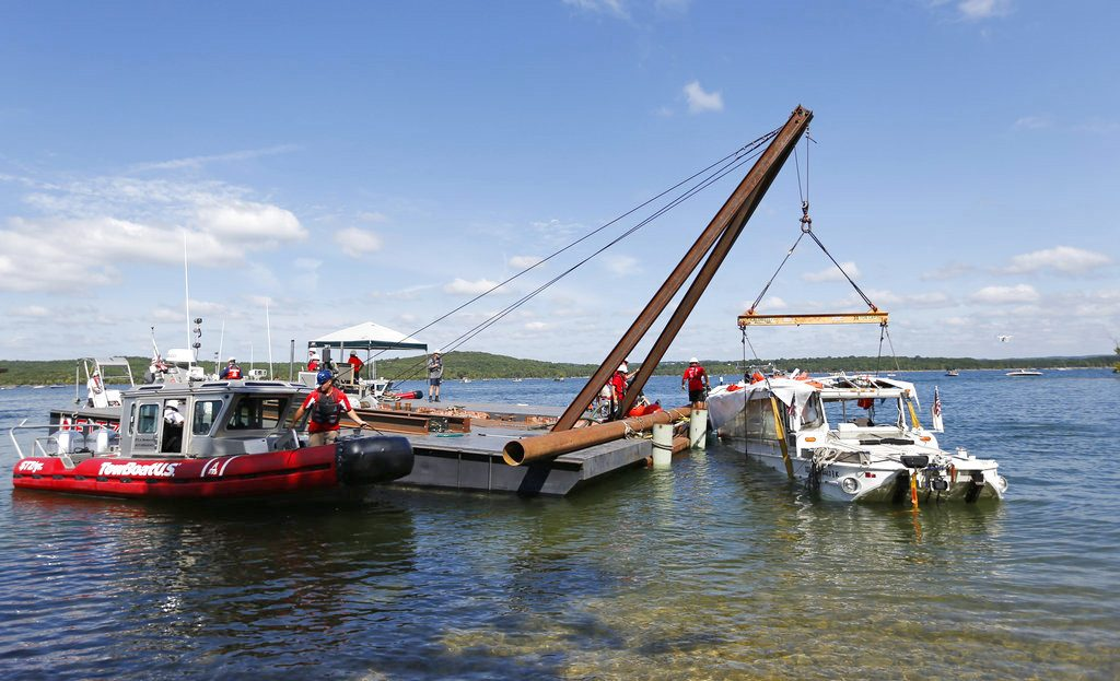 A barge crane raises the duck boat that sank in Table Rock Lake in Branson, Mo. The boat went down last Thursday evening after a thunderstorm generated near-hurricane-force winds.