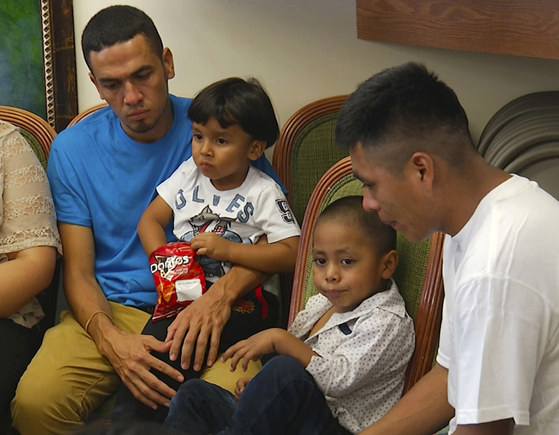 In this image taken from video, Javier Garrido Martinez, left and Alan Garcia, right, sit with their 4-year-sons at a news conference in New York on Wednesday The men were reunited with their children after almost two months of separation, Authorities took their boys them when they stopped at the U.S. southern border.