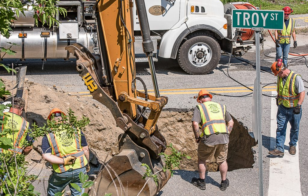 Auburn Public Works employees examine a large sinkhole at the end of Troy Street in Auburn on Friday, July 27, 2018. A sudden downpour Thursday afternoon caused extensive flooding in the city.