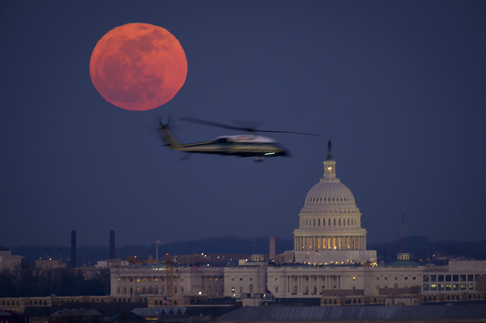 A United States Marine Corps helicopter is seen flying through this scene of the full Moon and the U.S. Capitol in 2012.