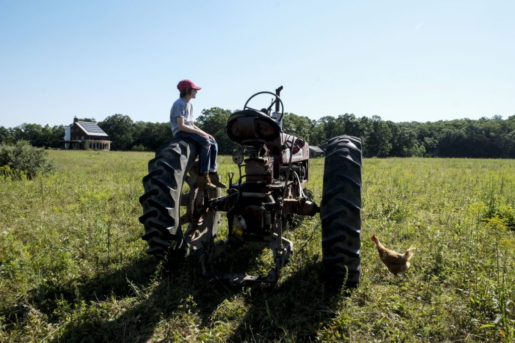 Silas Yates, 11, hangs out on his father's tractor at Broomgrass in Gerrardstown, W.Va., on July 19, 2018. MUST CREDIT: Washington Post photo by Bonnie Jo Mount.