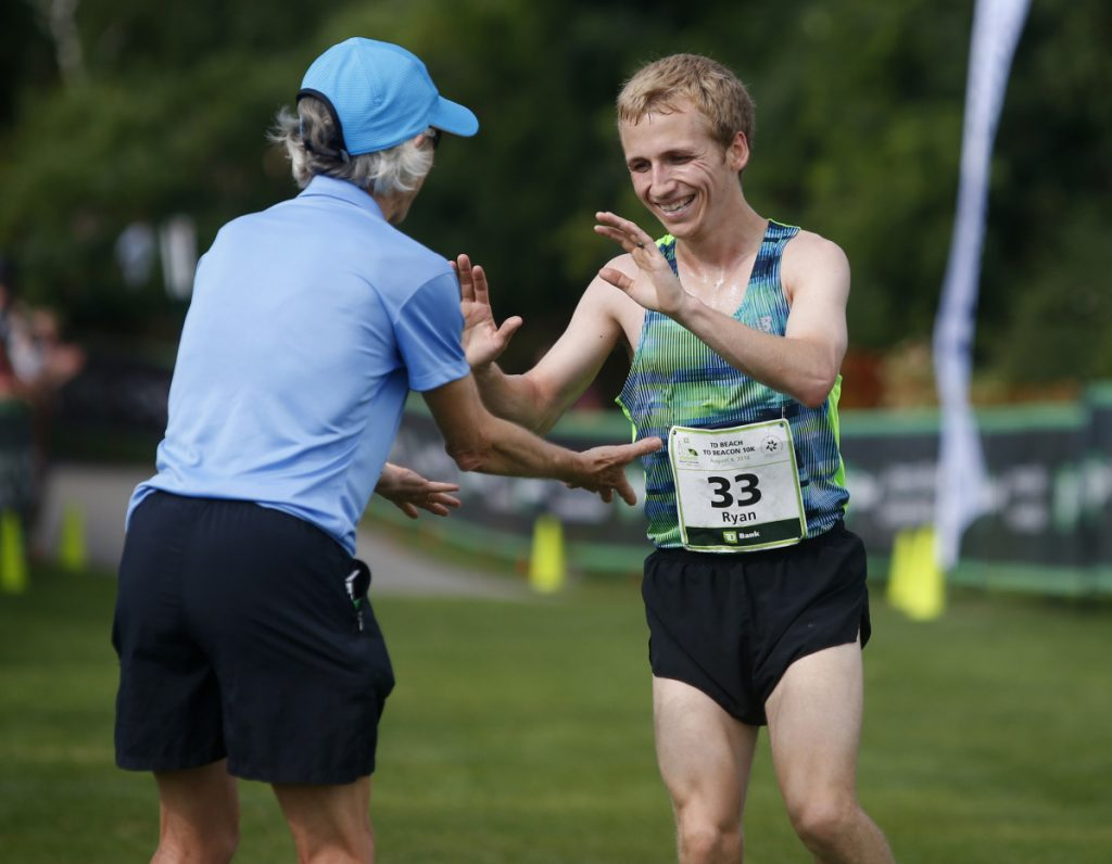 Ryan Smith of Farmington is met by race founder Joan Benoit Samuelson as finishes first among Maine runners at the 2018 TD Beach to Beacon 10K on Saturday in Cape Elizabeth. (Photo by Derek Davis/Staff Photographer)