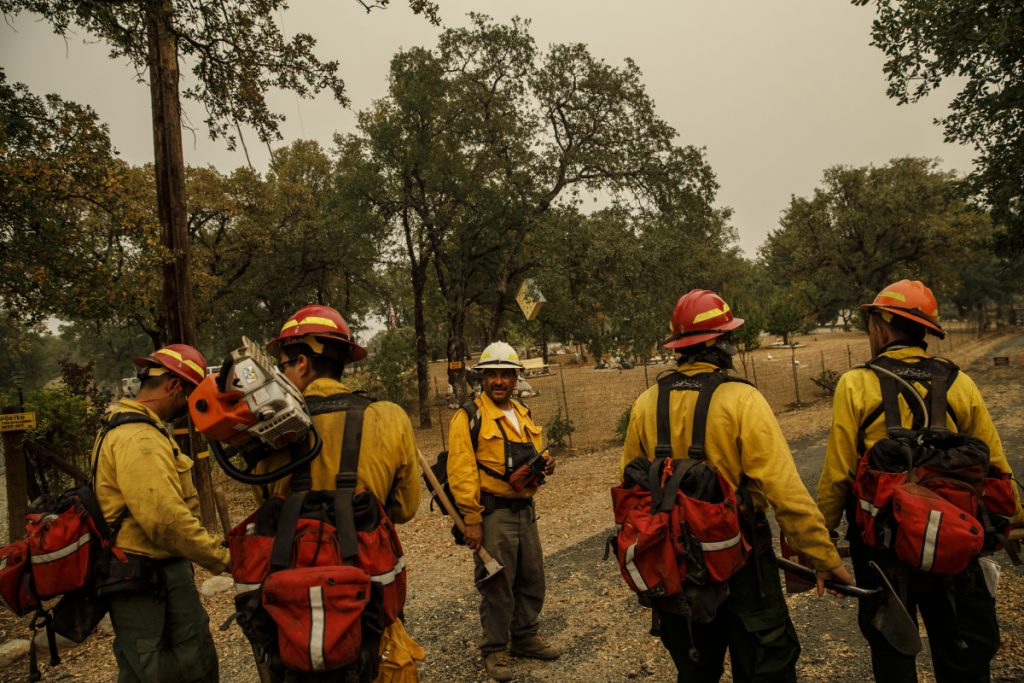 """Frederico Rocha Sr., center, leads his firefighters as they mop up hot spots near homes in Redding, Calif., on July 30. """"When people appreciate what we do, it makes us feel good,"""" Rocha said. """"Even at stores, people thank us and they're happy we're helping."""""""