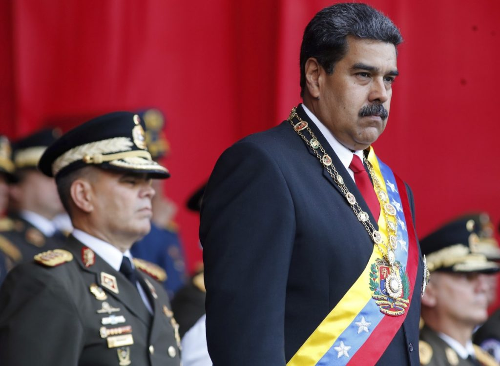 Associated Press/Ariana Cubillos FILE - In this  May 24, 2018 file photo, Venezuela's President Nicolas Maduro watches a military parade, alongside his Defense Minister Vladimir Padrino Lopez, behind, at Fort Tiuna in Caracas, Venezuela on May 24. State television in Venezuela showed President Maduro abruptly cutting short a speech on Saturday, Aug. 4, causing hundreds of soldiers present to break ranks and scatter.(AP Photo/Ariana Cubillos, File)