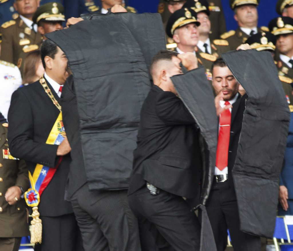 Security personnel try to shield Venezuelan President Nicolás Maduro, at left, on Saturday during an incident involving the detonation of armed drones as he gave a speech in Caracas.