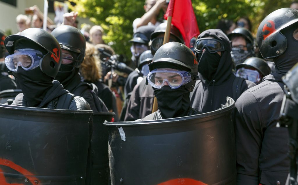 Dressed for battle in helmets and protective gear, counterprotesters prepare to clash Saturday with Patriot Prayer members at a rally in Portland, Ore. Officers formed a wall in the middle of a road to try to keep the groups separated.