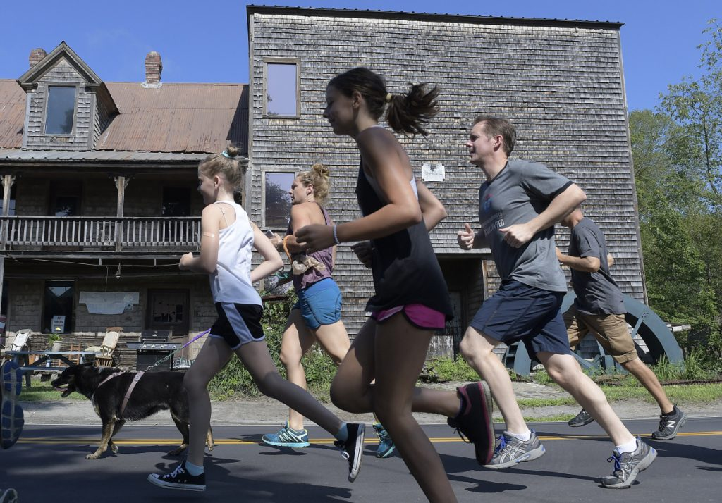 Runners sprint past the old grist mill Sunday in downtown Mount Vernon at the start of the Loon Lap, a 5K walk and run around Minnehonk Lake. Temperatures were in the mid-80s during the event, which raises funds for the Greater Minnehonk Lake Association and Mount Vernon Community Partnership.
