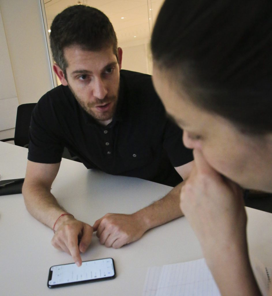 Jon Schlossberg, left, CEO of Even, an Oakland, Calif.-based fintech company that helps people predict cash flow problems and be paid when they want, shows a demonstration of the service.