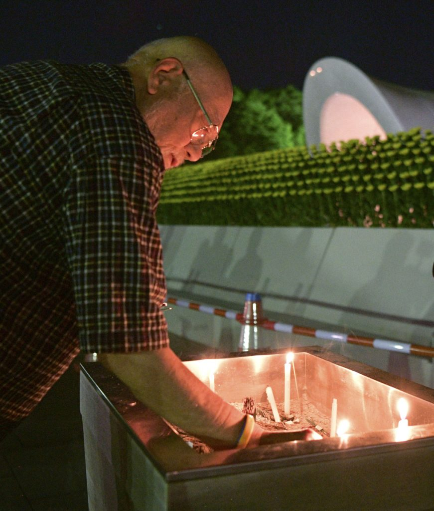 A man burns a stick of incense at the cenotaph dedicated to the victims of the atomic bombing at Hiroshima Peace Memorial Park in Hiroshima, western Japan, early Monday, marking the 73rd anniversary of the attack. (Yohei Nishimura/Kyodo News via AP)