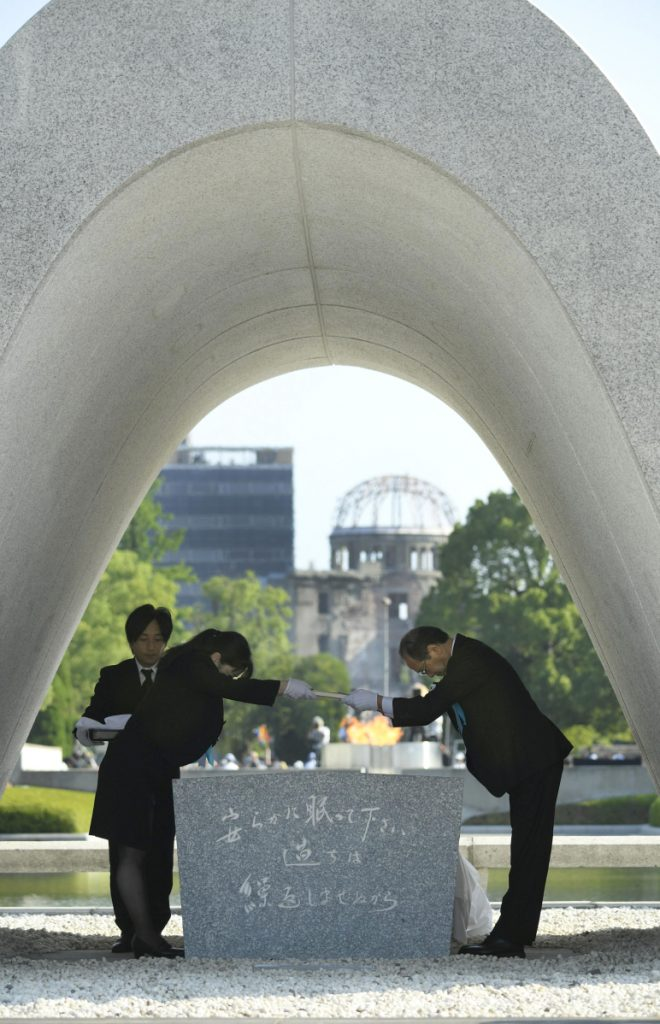 Hiroshima Mayor Kazumi Matsui, right, dedicates the list of the victims of atomic bombing to the cenotaph during a ceremony to mark the 73rd anniversary of the bombing at Hiroshima Peace Memorial Park in Hiroshima, western Japan, Monday. Matsui raised concerns in his peace address about the rise of egocentric policies in the world and warned against the idea of nuclear deterrence as a threat to global security. The Atomic Bomb Dome is seen in the background. (Yohei Nishimura/Kyodo News via AP)