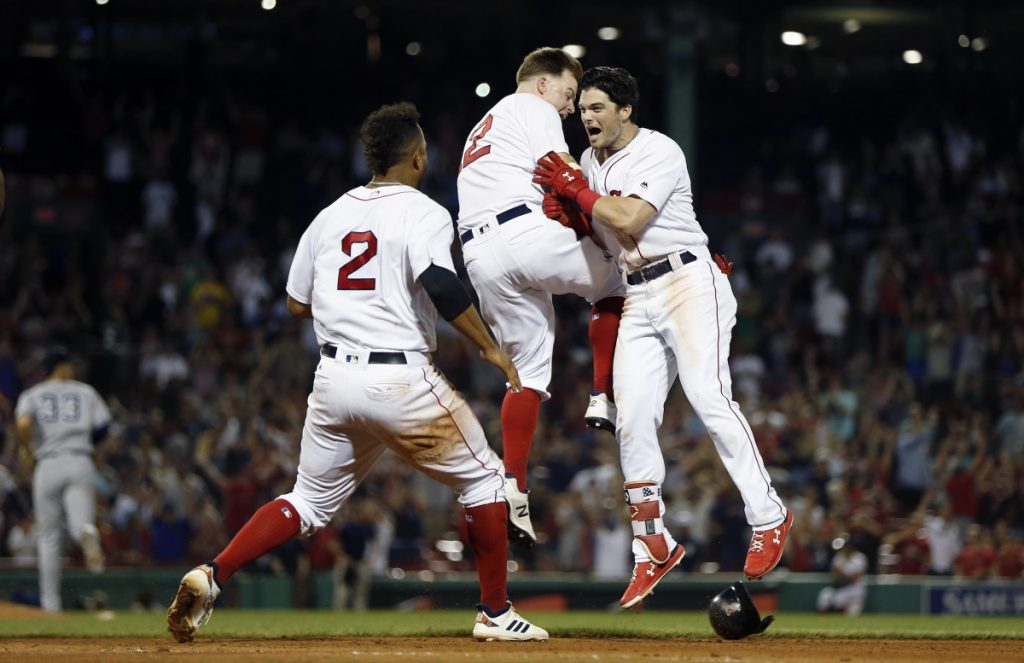 Boston Red Sox's Andrew Benintendi, right, celebrates his winning RBI single with Brock Holt, center, and Xander Bogaerts during the 10th inning Sunday night against the Yankees in Boston.