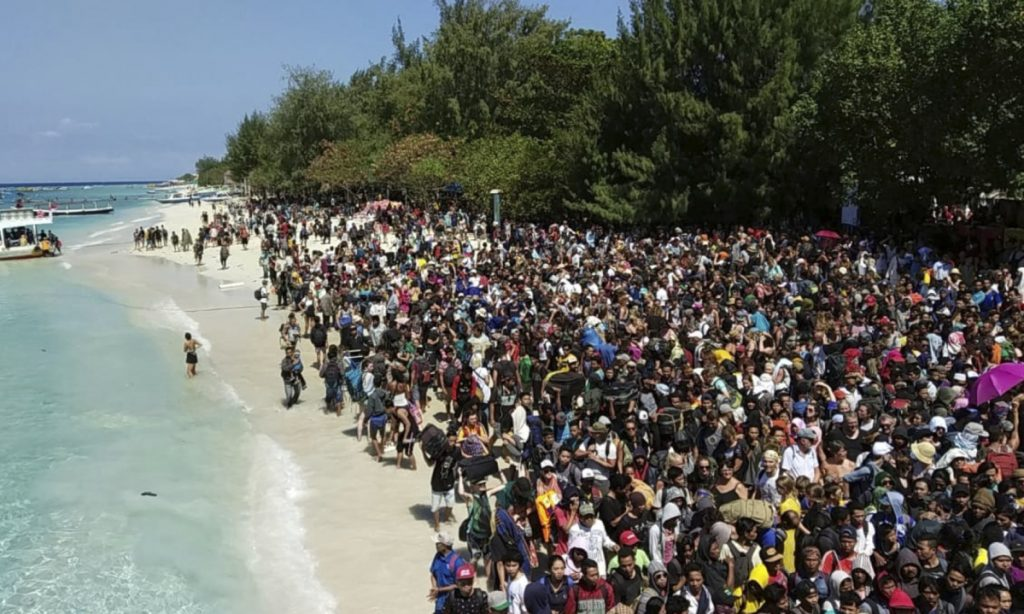 Tourists affected by a strong earthquake wait to be evacuated on Gili Trawangan Island in Indonesia on Monday.