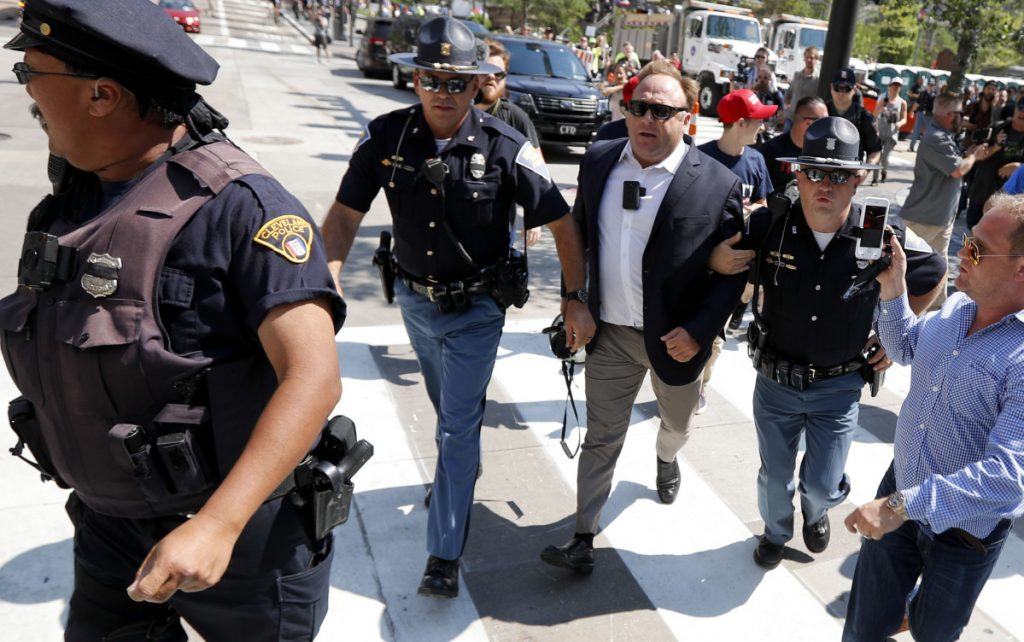 Conspiracy theorist Alex Jones, center right, is escorted by police out of a crowd of protesters outside the Republican National Convention in Cleveland in 2016. Facebook has taken down four pages belonging to Jones for violating its hate speech and bullying policies, but Twitter is leaving his material on its platform.
