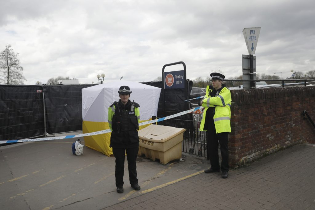 FILE - In this March 13, 2018, file photo, Police officers guard a police tent covering a supermarket car park pay machine near the spot where former Russian spy Sergei Skripal and his daughter were found critically ill following exposure to the Russian-developed nerve agent Novichok in Salisbury, England, in March. The United States will impose sanctions on Russia for the country's use of a nerve agent in the assassination attempt on the Skripals.