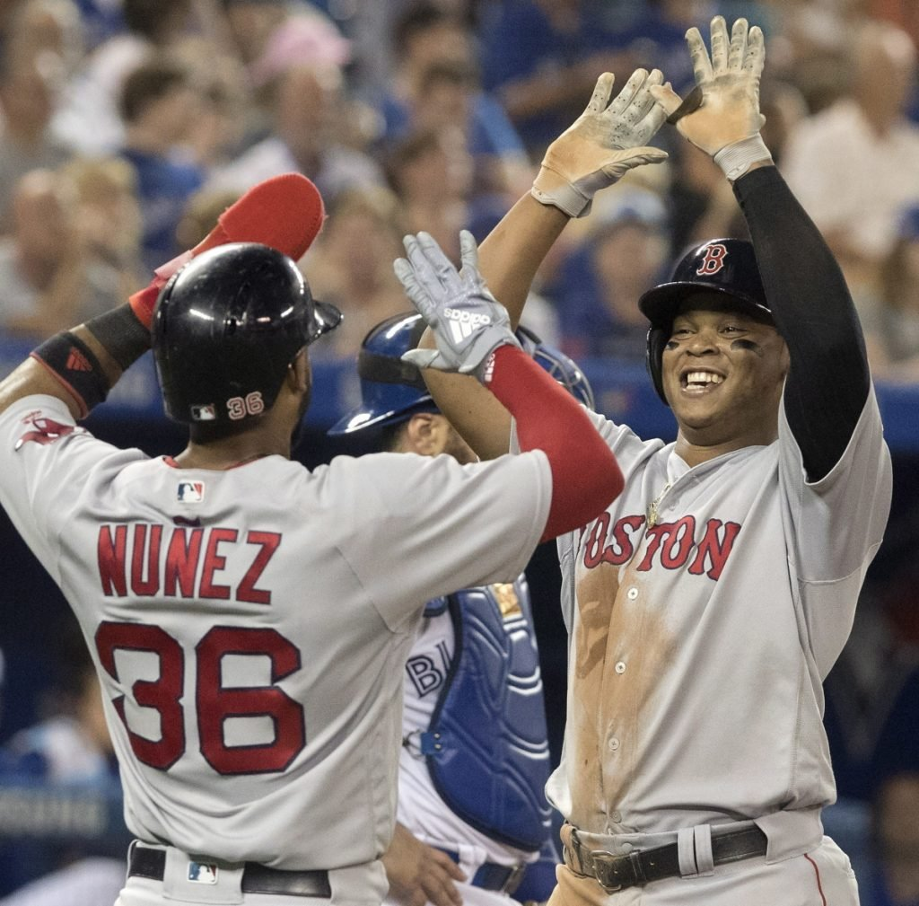 Rafael Devers gets a welcome-home high-five from Eduardo Nunez after hitting a two-run homer in the sixth inning Wednesday night in Toronto.