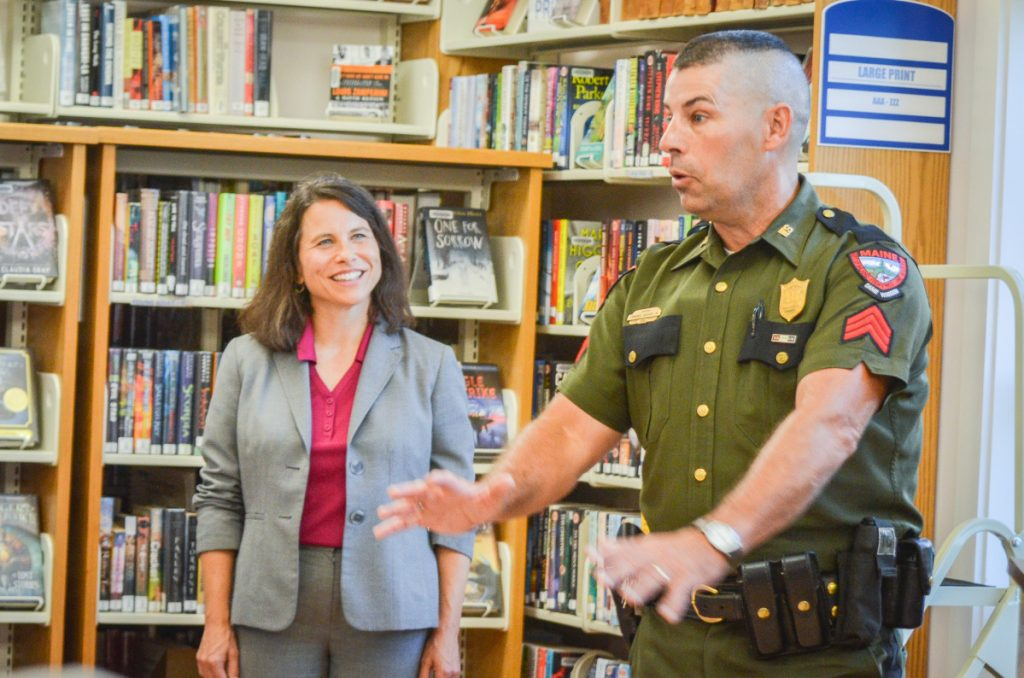 District Attorney Meaghan Maloney listens as Maine game warden Sgt. Terry Hughes describes the night he arrested the North Pond Hermit to a crowd at the Belgrade Public Library.