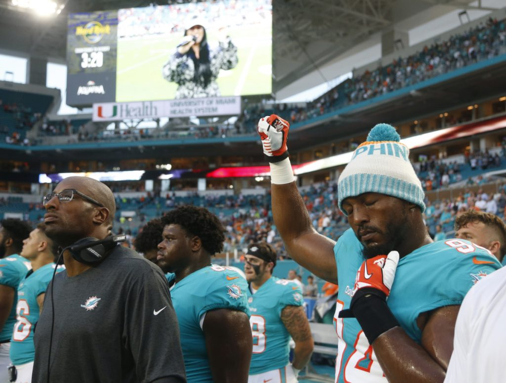 Miami Dolphins defensive end Robert Quinn raises his right fist during the singing of the national anthem, before the team's NFL preseason football game against the Tampa Bay Buccaneers on Thursday in Miami.