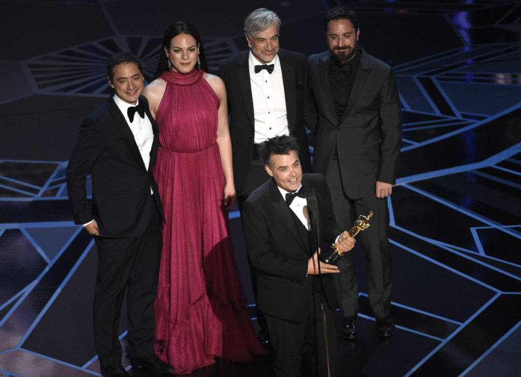 "FILE - In this March 4, 2018 file photo, Sebastian Lelio, foreground center, and Juan de Dios Larrain, background from left, transgender actress Daniela Vega, Francisco Reyes, and Pablo Larrain accept the award for best foreign language film for ""A Fantastic Woman"" at the Oscars in Los Angeles."