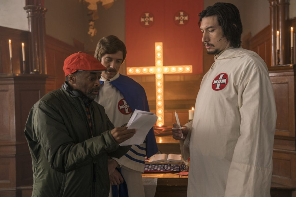 "This image released by Focus Features shows director Spike Lee, left, with actors Topher Grace, center, and Adam Driver on the set of Lee's film ""BlacKkKlansman."" Lee is releasing his film this weekend, a year after the violent clashes in Charlottesville in which anti-racism activist Heather Heyer was run over and killed. Lee's film is about an earlier chapter in white supremacism and the Ku Klux Klan: when African-American police detective Ron Stallworth infiltrated a Colorado Springs, Colorado, chapter of the KKK in 1979."