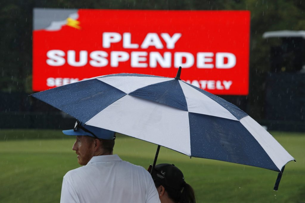 Patrons stand under an umbrella as play was suspended for the rest of the day during the second round of the PGA Championship golf tournament at Bellerive Country Club on Friday in St. Louis. Play was suspended due to heavy rain.