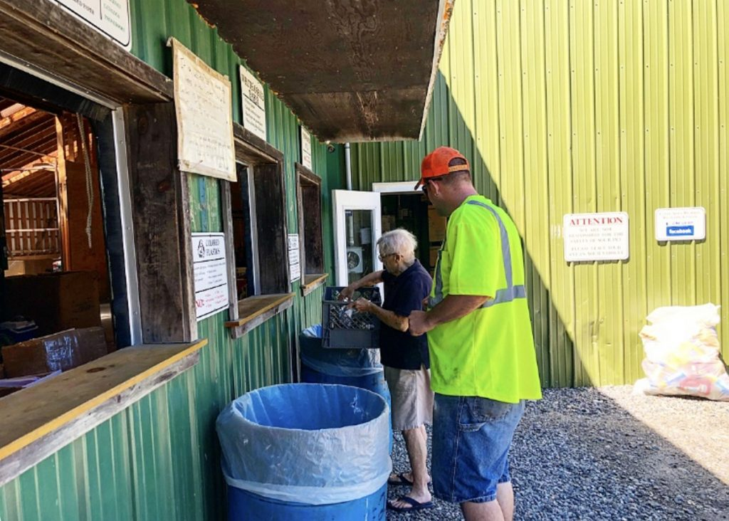 "Unity Area Regional Recycling Center manager Stanley Besancon helps Betty Gross of Unity sort her recyclables Friday in Thorndike. ""The market has been bad for about a year now,"" he said, ""especially with China reducing the imported recycling from the United States."""